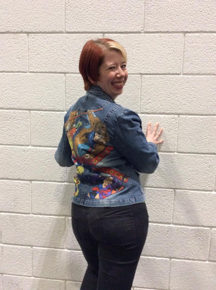 A woman wearing a denim jacket with X-Men themed fabric on the back.