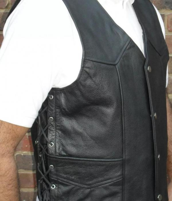 A man wearing a black leather waistcoat and a white short sleeved shirt.