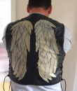 A man wearing a black leather waistcoat with wings on the back.